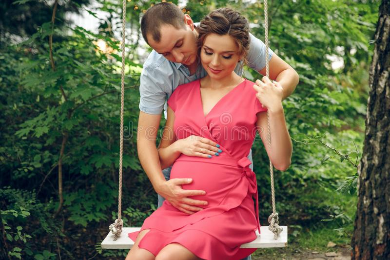 A pregnant young woman and her husband. A happy family sitting on a swing, holding belly. pregnant woman relaxing in the park. royalty free stock photos