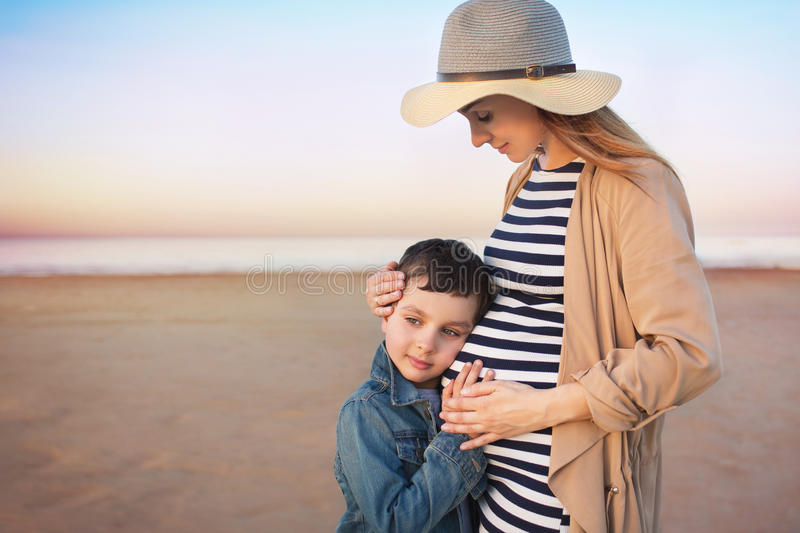 Pregnant young woman with his little son stands on a beach and puts hands on a belly stock photos