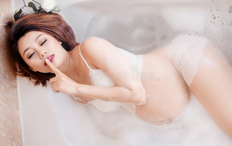 Pregnant young woman relaxing in bath stock photo