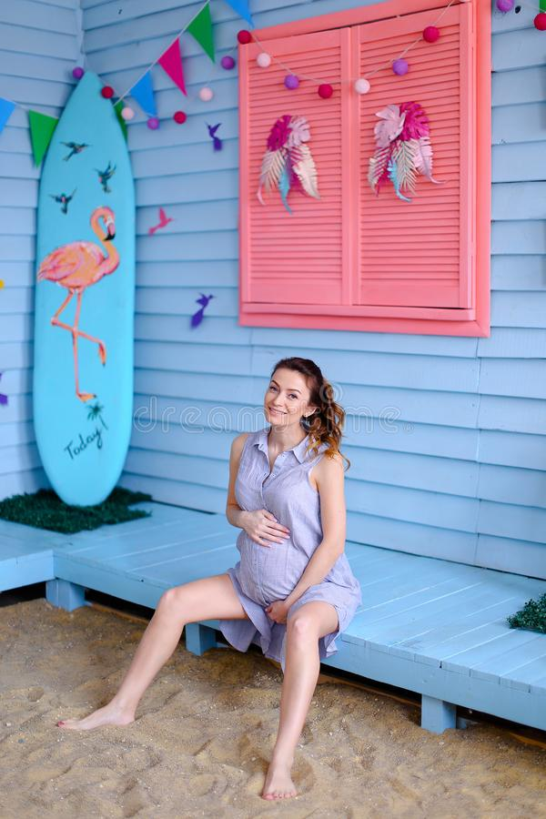 Pregnant young woman sitting on bench near children houe and holding belly. royalty free stock photos