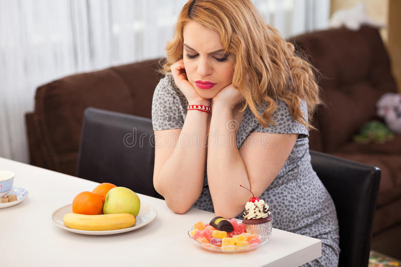 Pregnant young woman. Trying to decide whether to eat fruits or sweets, sitting at the kitchen table royalty free stock photography