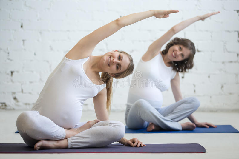 Pregnant young women doing prenatal yoga. Bending in easy pose. Pregnancy Yoga, Fitness concept. Two beautiful young pregnant yoga models working out indoor stock photo