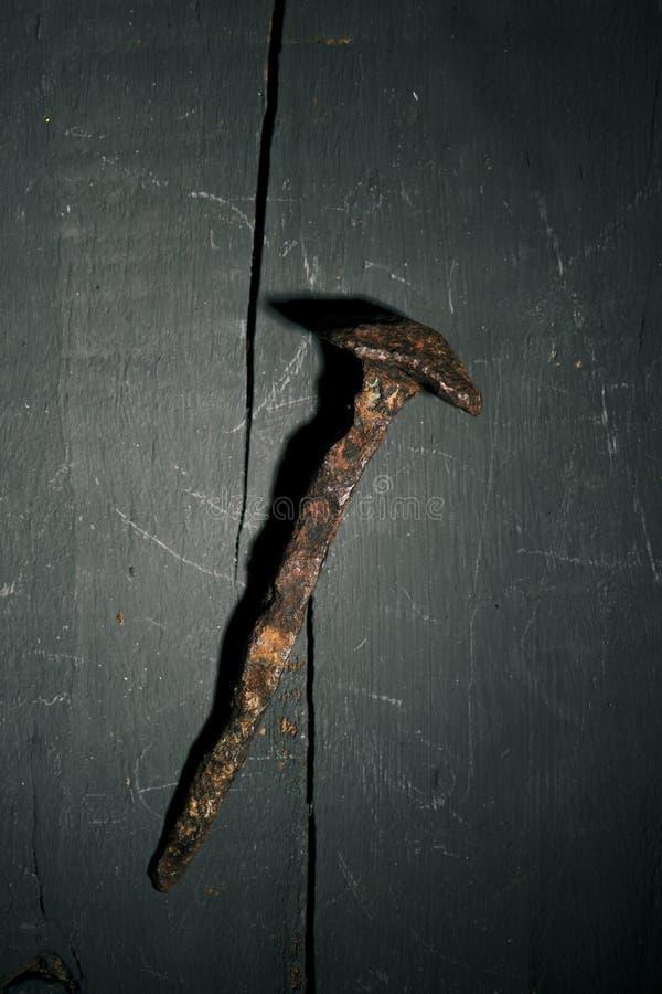 Prego oxidado em uma superfície de madeira rústica fotografia de stock