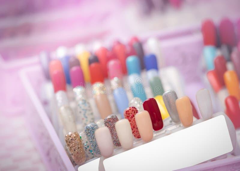 Pregos artificiais coloridos na loja do salão de beleza do prego Ajuste dos pregos falsos para que o cliente escolha a cor para o fotos de stock