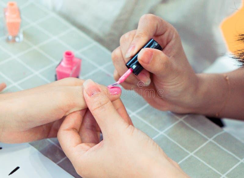 Pregos de uma pintura da menina com verniz para as unhas cor-de-rosa imagens de stock royalty free