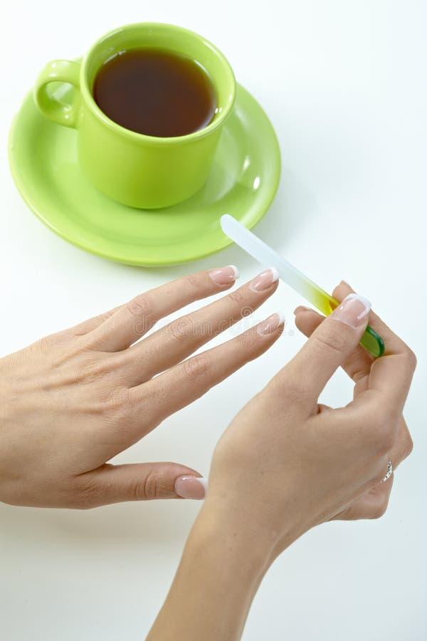 Pregos fêmeas do arquivamento da mão sobre o copo do chá fotografia de stock