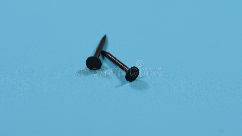 Pregos pretos pequenos em um fundo azul fotos de stock royalty free