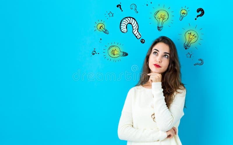 Pregunta con las bombillas con la mujer joven imagen de archivo