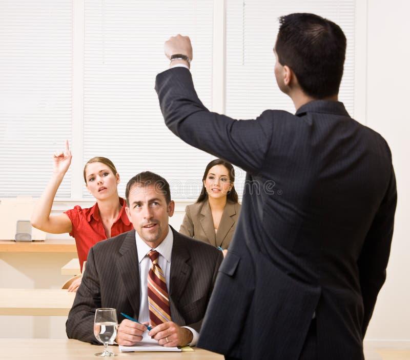Preguntas de contestación del hombre de negocios en la reunión imagenes de archivo