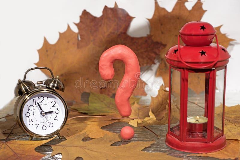 Pregunte la muestra en fondo de las hojas de otoño con la linterna de la vela imagen de archivo