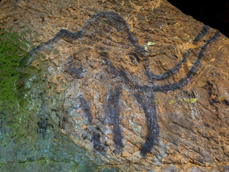 Prehistoric art of mammoth in sandstone cave. Spotlight shines on historical painting. Black carbon mammoth on sandstone wall. Paint of human hunting stock photos