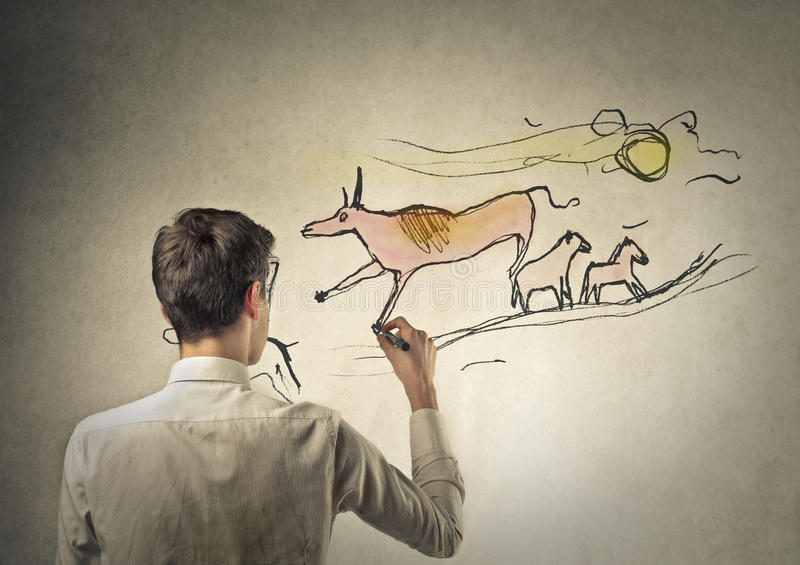 Prehistorical drawing. A man is doing a prehistorical drawing on a wall stock image