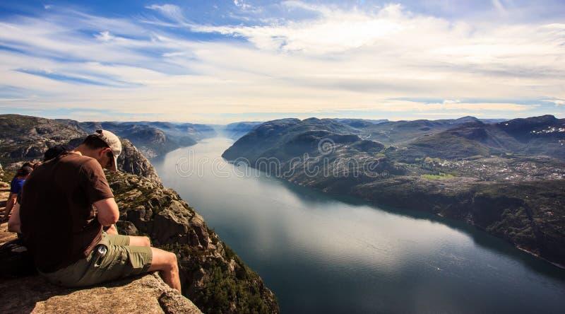 Preikestolen, Noruega - 23 de julio de 2016: Los turistas miran a la visión majestuosa desde la roca del púlpito del predicador d foto de archivo