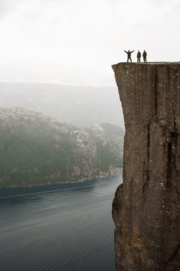 Preikestolen - zadziwiaj?ca ska?a w Norwegia Dziewczyny pozycja na falezie nad chmury obraz stock