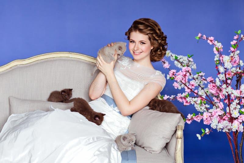 Prejuízo do ¡ de Ð e menina bonita no vestido branco que senta-se em um sofá sobre foto de stock