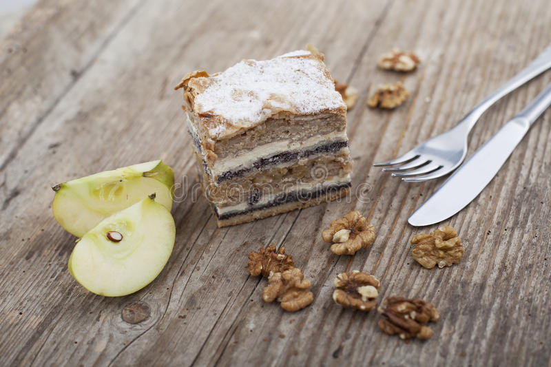 Prekmurska hibanica over mura moving layered cake. On wooden surface with apple royalty free stock photo