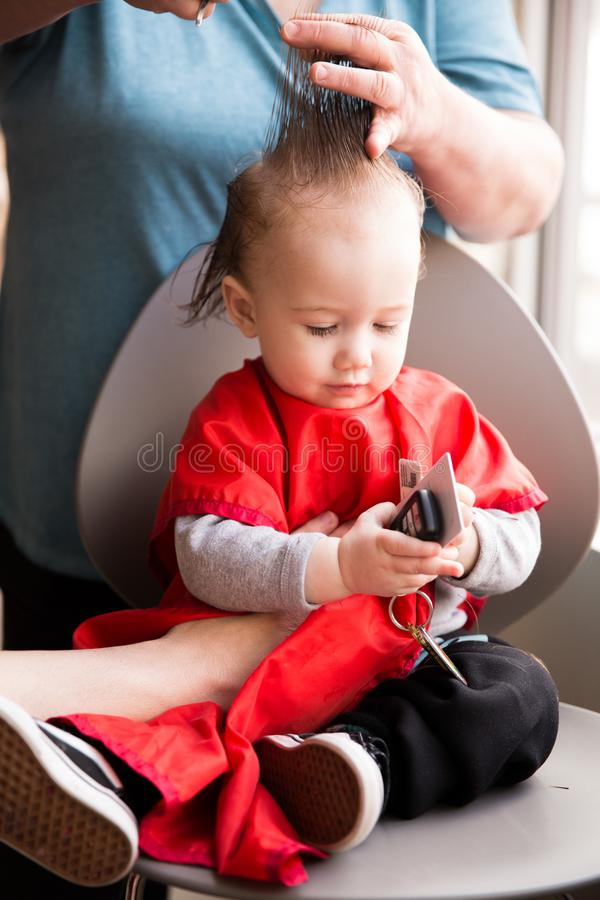 Première coupe de cheveux pour le garçon d'enfant en bas âge images stock