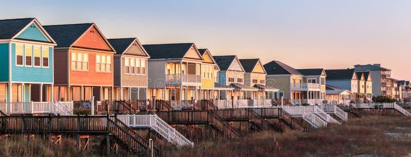 Première lumière sur la rangée des maisons de plage colorées photos stock