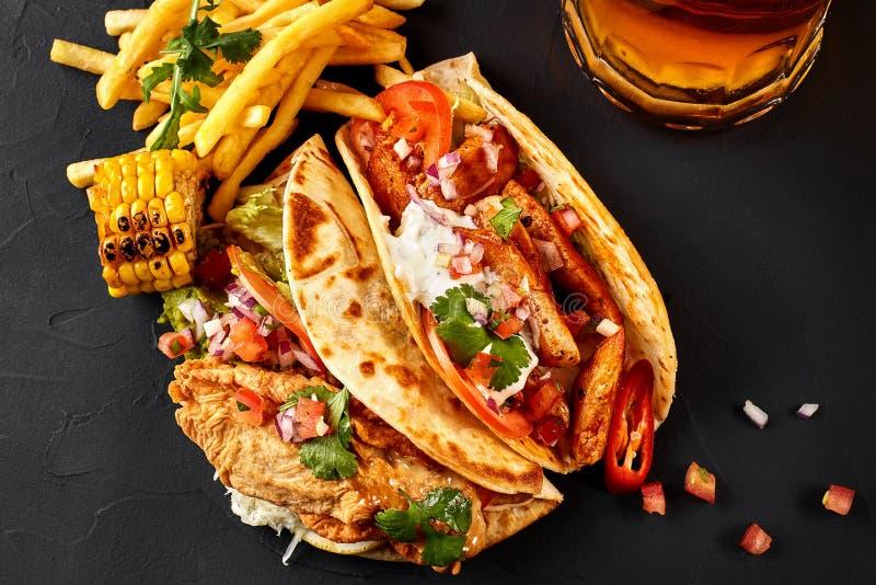 Première tortilla de maïs avec le filet grillé de poulet, deuxième avec le filet de poissons, pommes frites, sauce et bière sur l photos libres de droits
