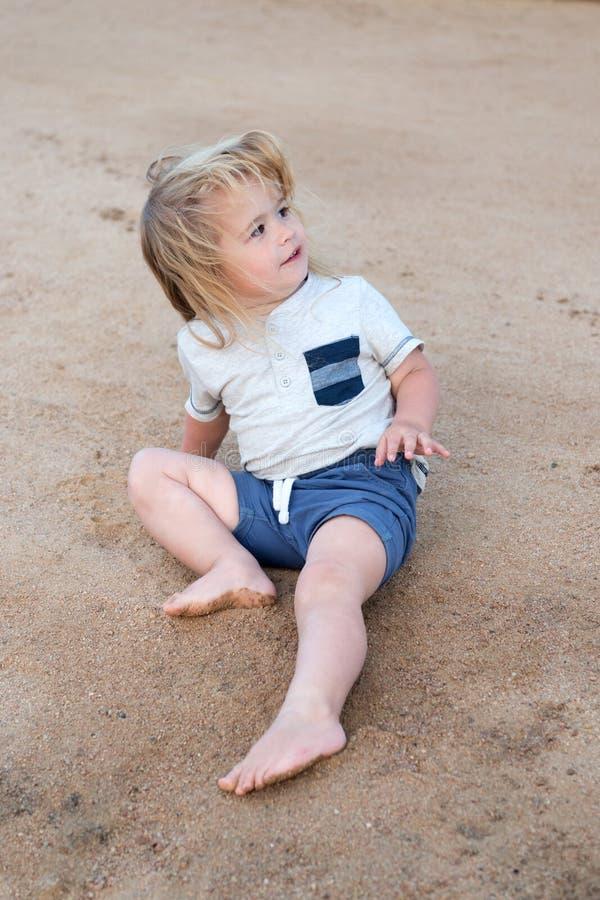 Premières vacances avec des astuces et le conseil d'enfant Garçon que peu d'enfant se reposent sur le sable L'enfant en bas âge a photos stock