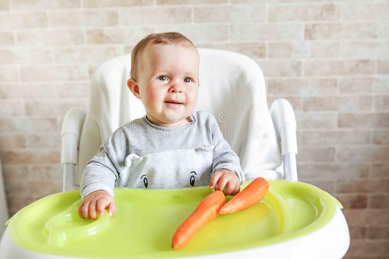 Premi?re nourriture solide pour le jeune gar?on Carotte organique fra?che pour le d?jeuner v?g?tal Le b?b? mangent des l?gumes Nu photographie stock