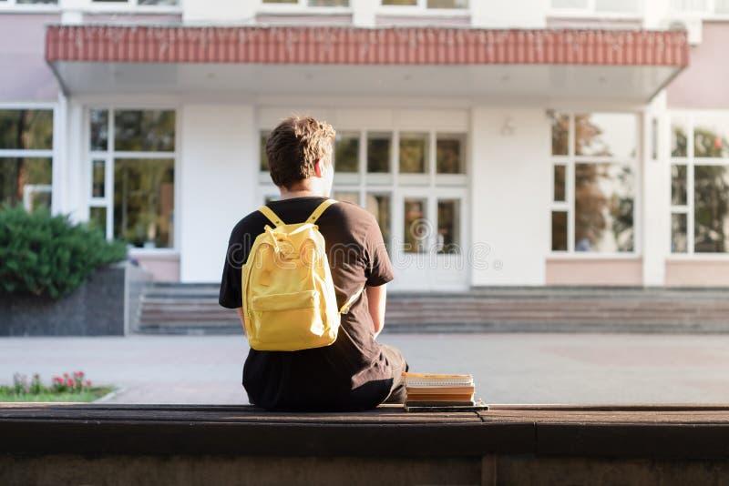 Premier étudiant d'année s'asseyant en dehors d'un facili d'université ou d'école photographie stock