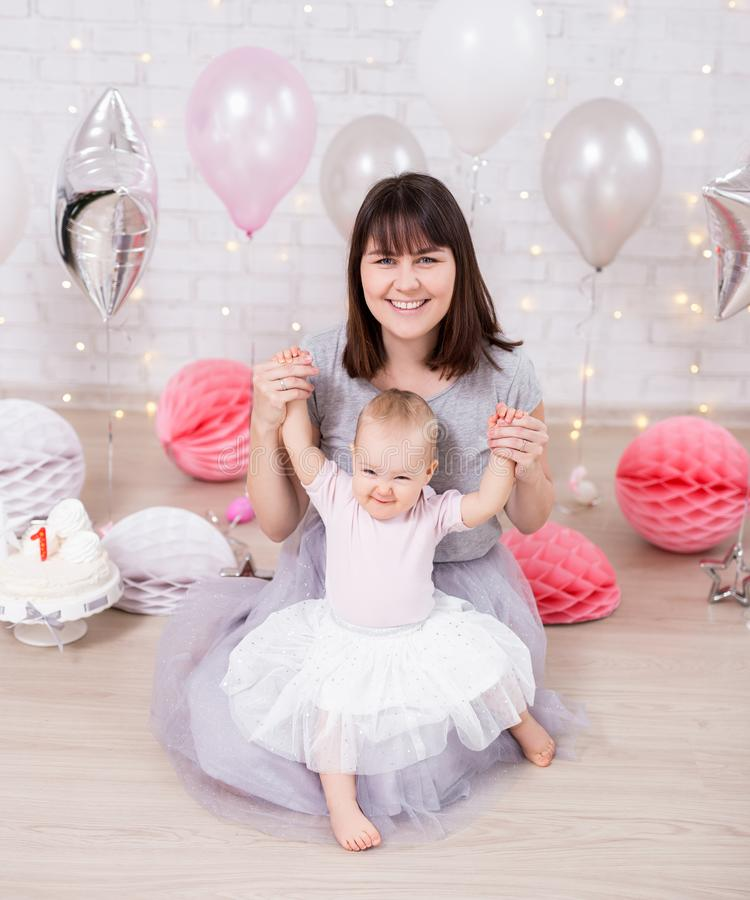 Premier concept d'anniversaire - bébé mignon s'asseyant avec la mère dans la chambre décorée image libre de droits