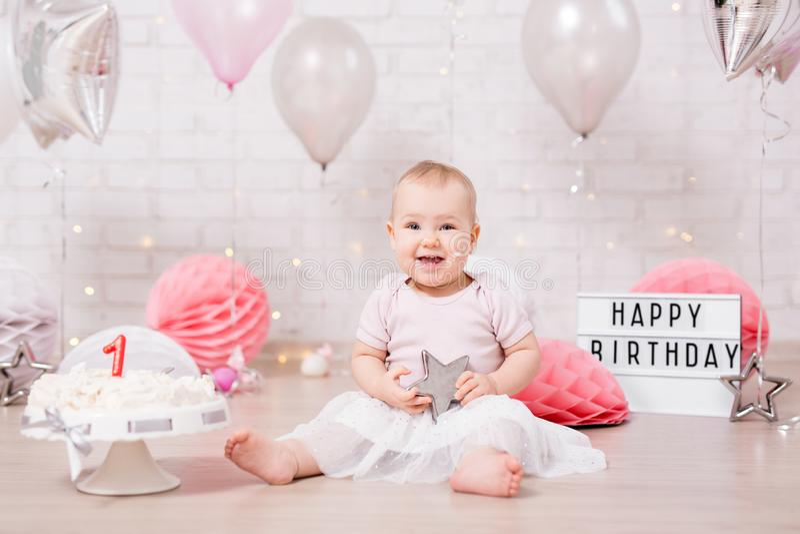 Premier concept d'anniversaire - fille sale drôle et gâteau d'anniversaire heurté avec des lumières et des ballons image stock