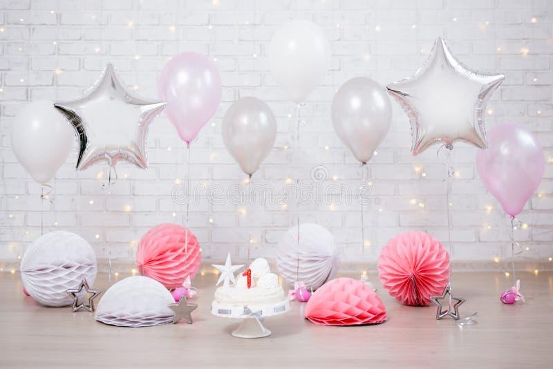Premier fond d'anniversaire - pièce décorée avec le gâteau et les ballons au-dessus du mur blanc photographie stock