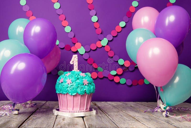 Premier gâteau d'anniversaire avec une unité sur un fond pourpre avec les boules et la guirlande de papier photographie stock libre de droits