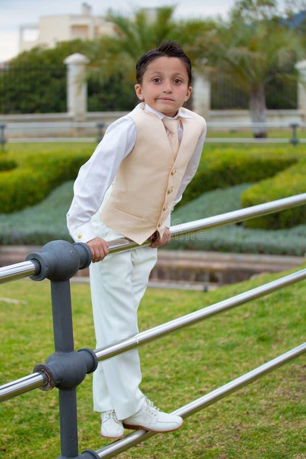 Premier garçon de communion de jeunes se penchant sur une barrière en métal images stock