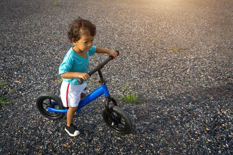 Premier vélo d'équilibre de jeu de jour d'enfant asiatique photos libres de droits