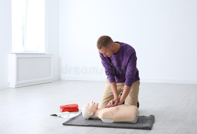 Premiers secours de pratique d'homme sur le mannequin photos stock
