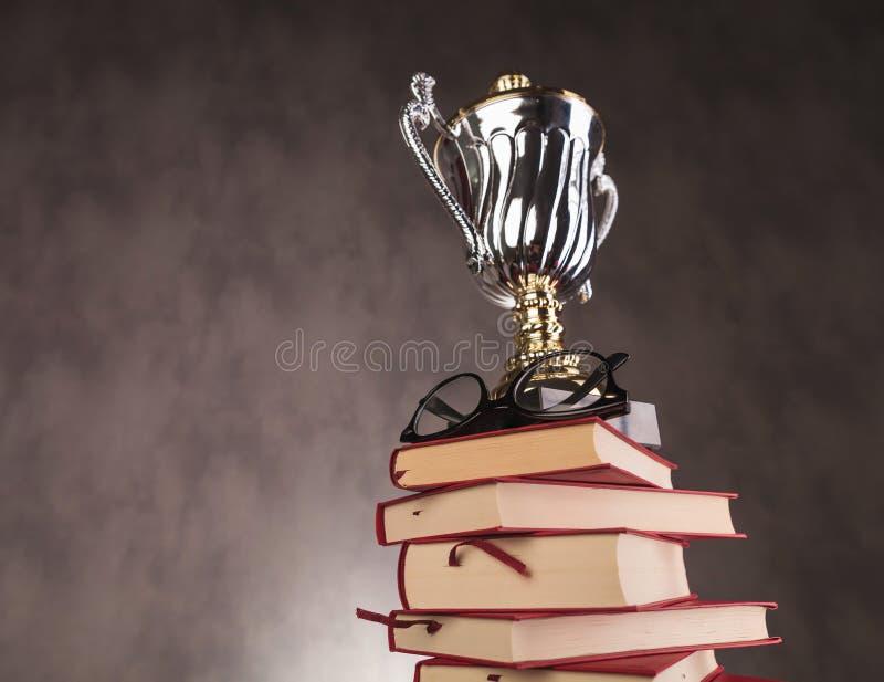 Premio de la taza del trofeo y vidrios encima de los libros imagen de archivo libre de regalías