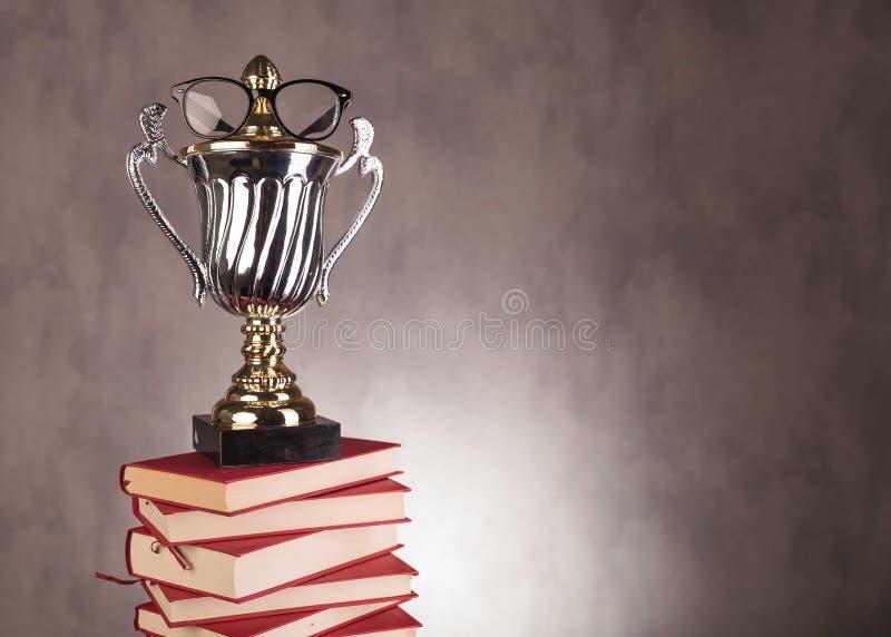Premio del campeón del estudiante con los vidrios en la pila de libros foto de archivo libre de regalías