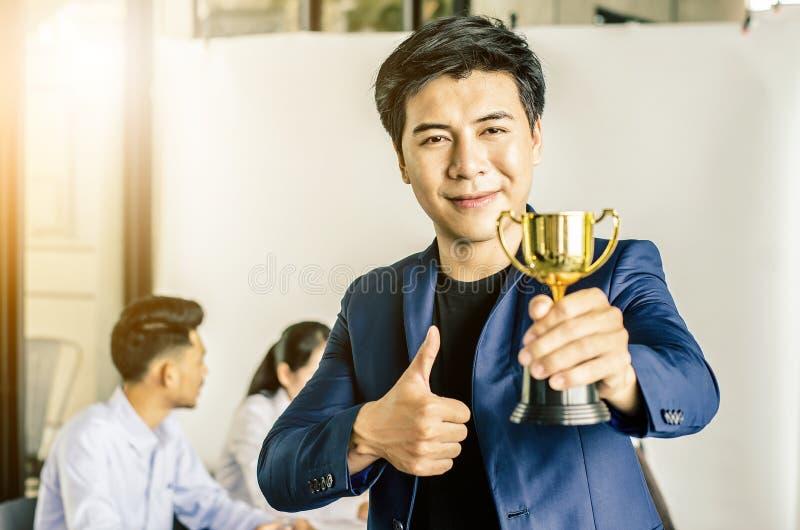 Premio del trofeo della tenuta dell'uomo d'affari per successo nell'affare fotografia stock libera da diritti