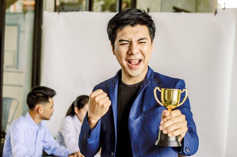 Premio del trofeo della tenuta dell'uomo d'affari per successo nell'affare, fotografia stock libera da diritti