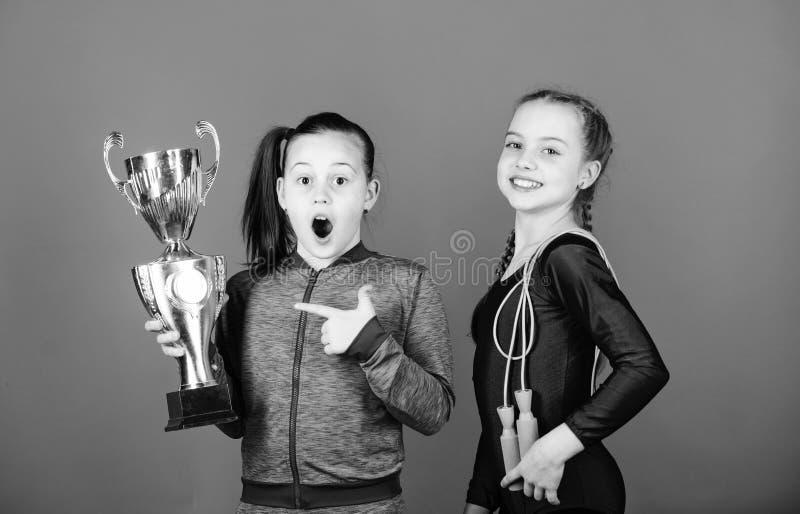 Premio meritato I bambini atletici delle ragazze celebrano la vittoria Ragazze atletiche con il calice dorato Campionato di vitto fotografie stock