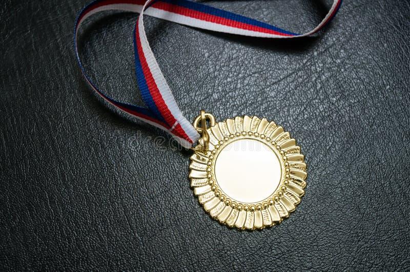 Premio per un vincitore - medaglia d'oro su fondo nero fotografie stock libere da diritti