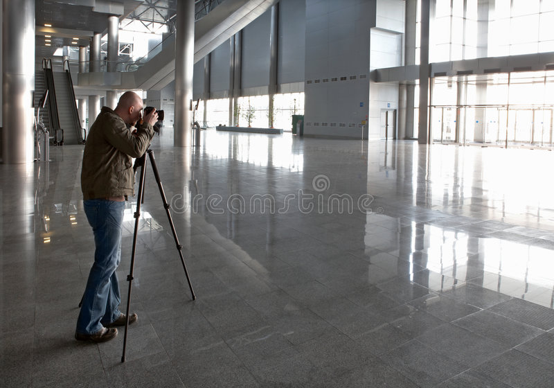 Premise photographing. The photographer photographs the big hall centre business stock photography
