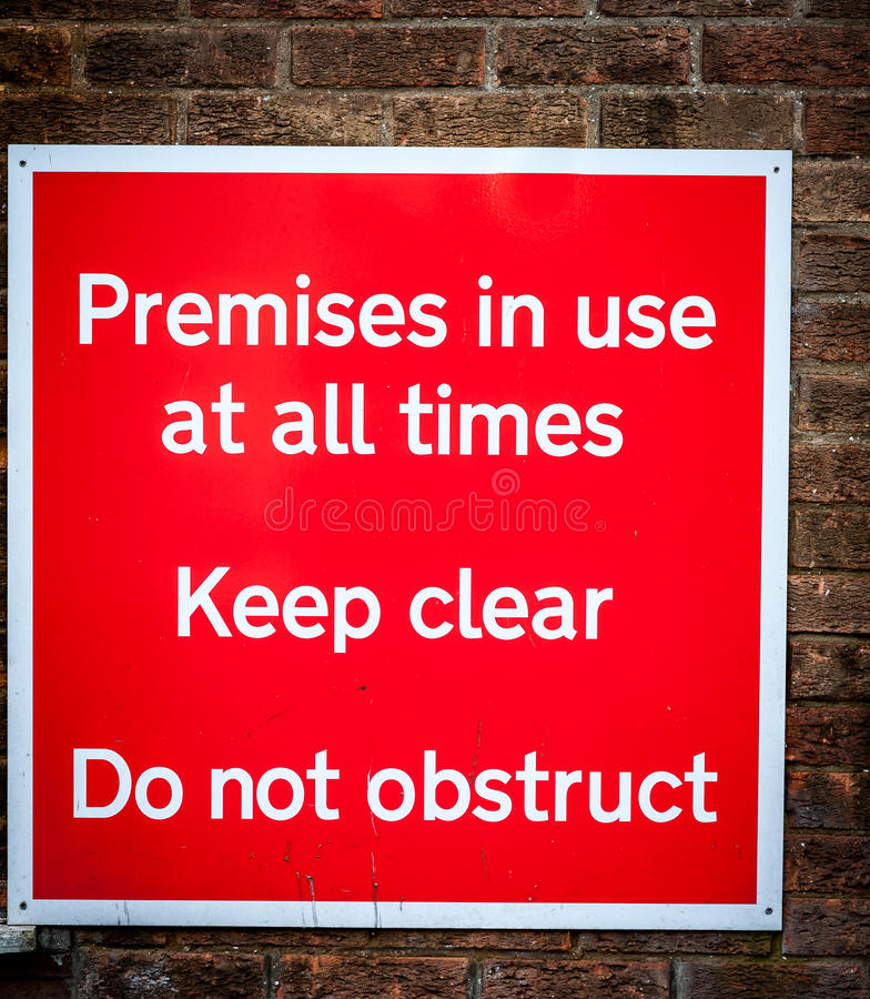 Premises in use sign. Large red metal sign declaring premises in use attached to a brick wall stock images