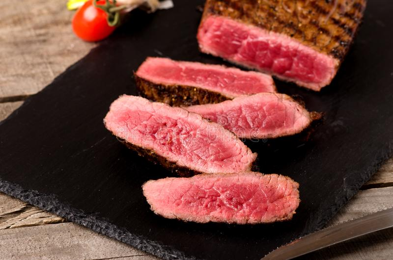 Premium beef rare steak sliced. On a gray wooden background royalty free stock photos