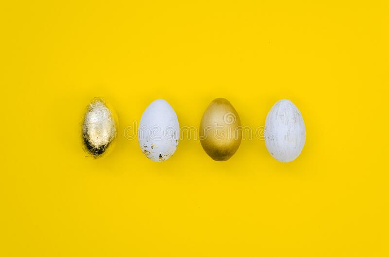 Premium gold Set of 4 Easter eggs isolated on yellow background Ester concept. Top view royalty free stock photography