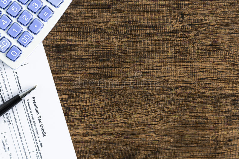 Premium tax credit form with calculator and pen on the wooden table stock image