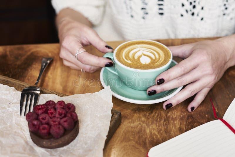 Prenant le déjeuner avec du café biscuit de chocolat à plat blanc et sucré dans un café ou un restaurant La femme remet à des pri photographie stock