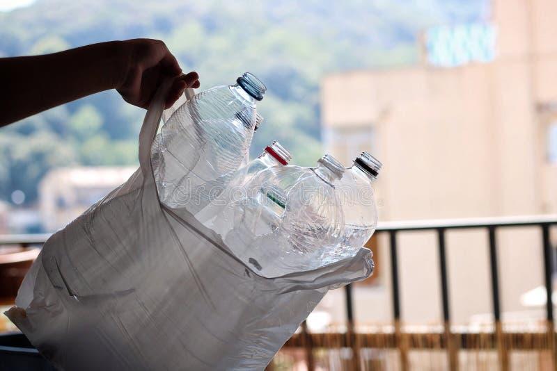 Prenant un sac avec les bouteilles en plastique à l'intérieur photographie stock