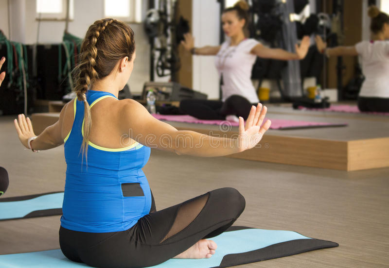 Prenatal yoga classes. Pregnant mother in yoga class doing relaxing movements stock photo