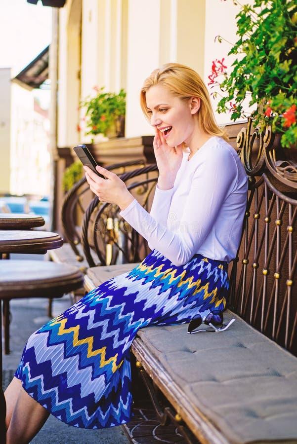 Prenda l'appuntamento Il fronte entusiasta della donna con lo smartphone crea l'appuntamento nella rete sociale ed aspetta il caf fotografia stock