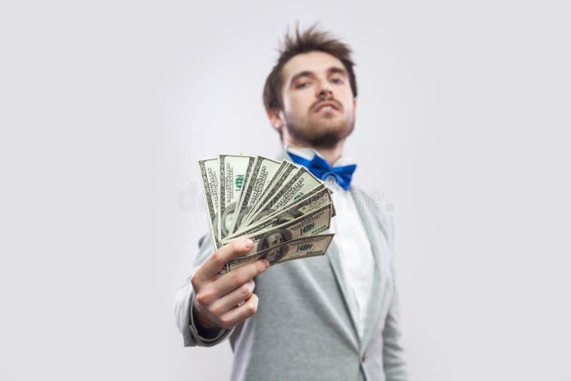 Prendalo! Il ritratto di giovane uomo d'affari attraente sicuro in cappotto grigio e nella condizione blu della cravatta a farfal fotografia stock libera da diritti