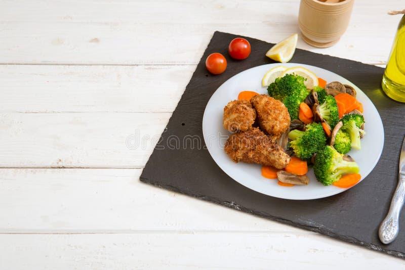 Prendedero asado a la parrilla del pollo adornado con bróculi, zanahorias y setas imagen de archivo
